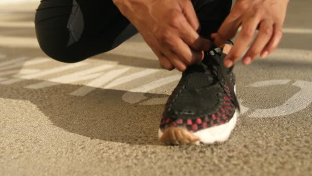 vidéos et rushes de coureur attachant ses chaussures - vue partielle