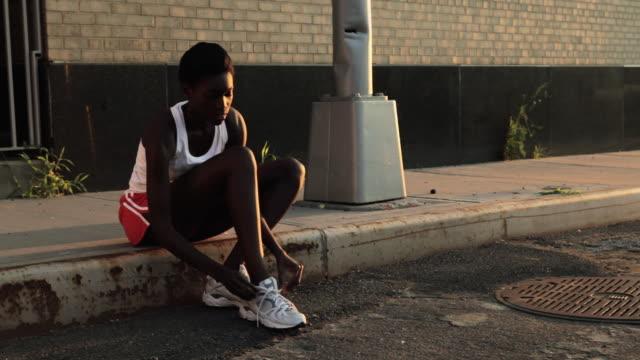 stockvideo's en b-roll-footage met runner tying shoelaces on sidewalk - gymbroek
