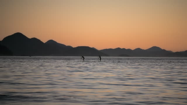 stockvideo's en b-roll-footage met runner wipes frame as two silhouetted men paddleboard off copacabana shore in slow motion - men