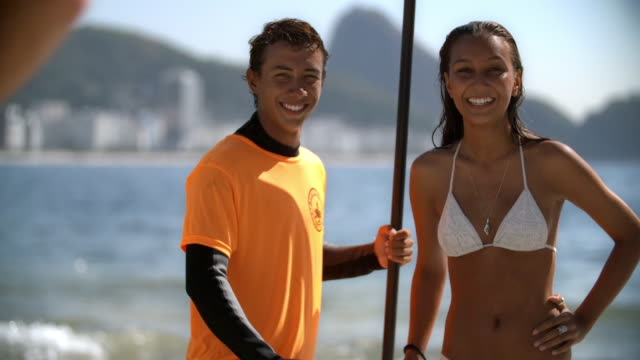 Runner wipes frame as young Brazilian paddleboarder and girlfriend smile for camera on sunny Copacabana Beach