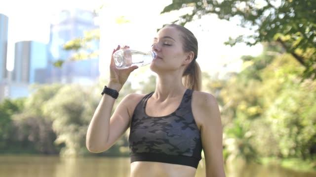 vídeos de stock, filmes e b-roll de corredor mulher bebendo água - refresco