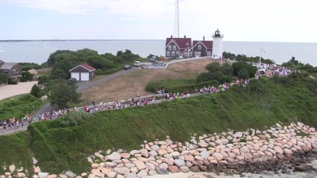 stockvideo's en b-roll-footage met runners around lighthouse aerial shot from falmouth road race on cape cod runners around lighthouse aerial cape cod on august 15 2010 - salmini