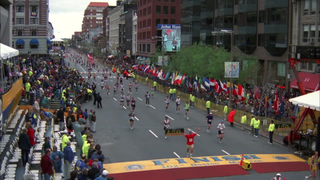 runners cross finish line at boston marathon as crowds cheer and clap, massachusetts; 1997 available in hd. - linea d'arrivo video stock e b–roll
