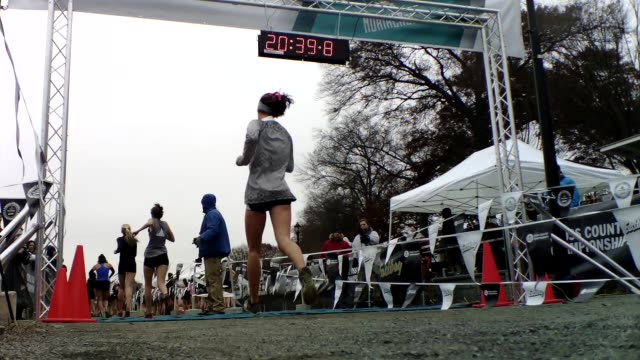 runners cross finish line, girls, low angle - salmini stock videos & royalty-free footage