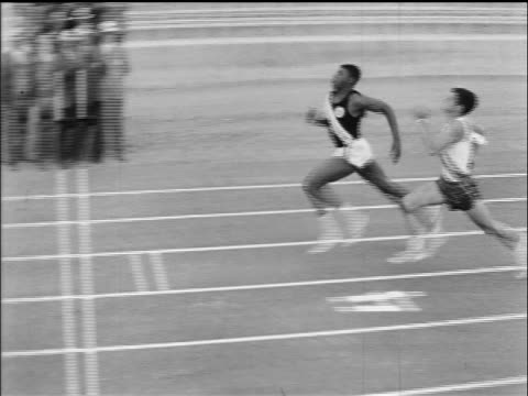 b/w 1965 slo mo ha runners crossing finish line / documentary - atletico video stock e b–roll