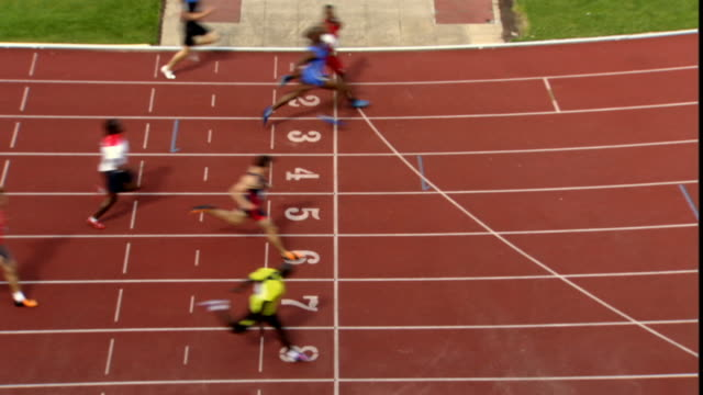 vídeos de stock e filmes b-roll de ha ws runners crossing finish line on sports track/ sheffield, england - acabar