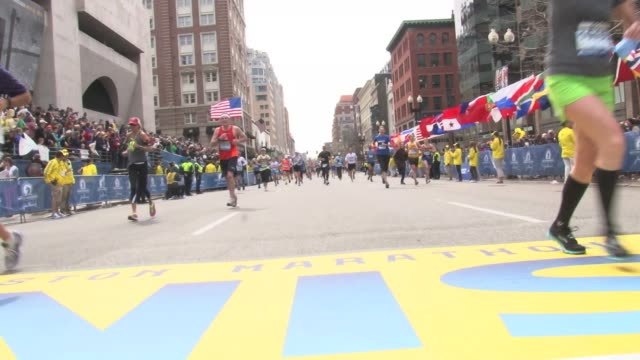 / runners crossing the finish line just before the bombing at the Boston Marathon / police officers climbing over fencing smoke and debris