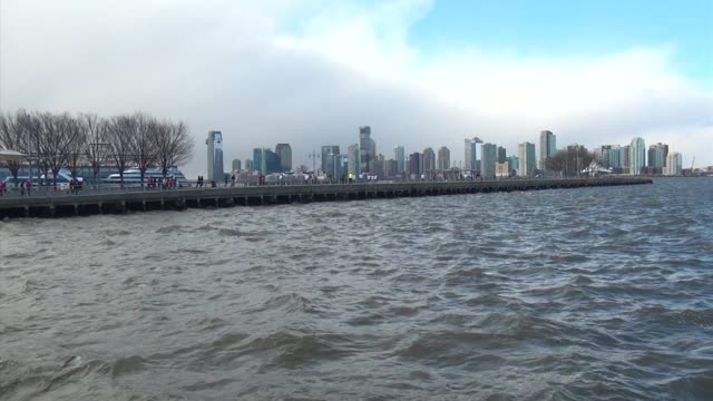 vídeos y material grabado en eventos de stock de runners head out to end of pier over hudson river waves in foreground severe weather - salmini