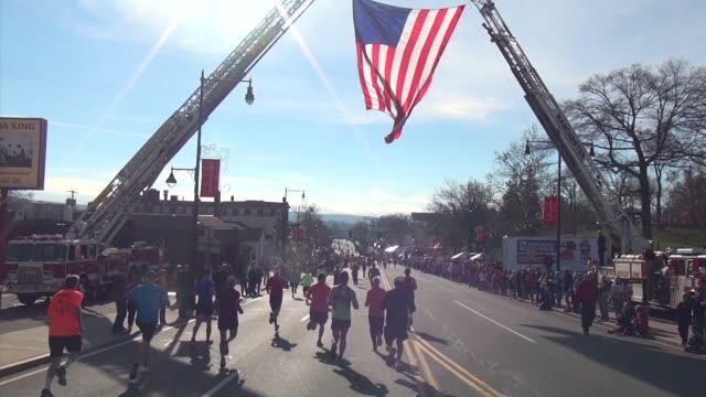 vidéos et rushes de runners head toward finish line under american flag - salmini