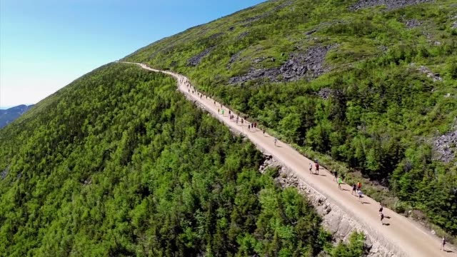 Runners head up mountain road aerial drone shot showing summit and elevation 74 miles with no level sections but it's only one hill