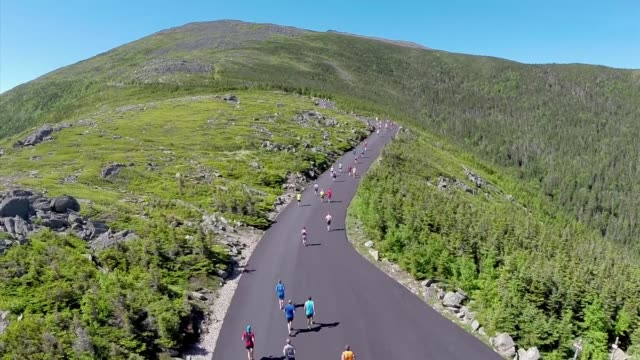 """runners head up mountain road, aerial drone shot showing summit and elevation. 7.4 miles with no level sections but """"it's only one hill"""". - trefferversuch stock-videos und b-roll-filmmaterial"""