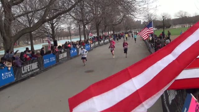 vidéos et rushes de runners in queens half marathon runners finishing with american flag in foreground - salmini