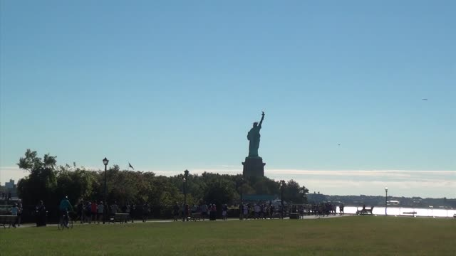 runners in road race head through liberty state park in jersey city with new york bay and the hudson river in background statue of liberty zoom out... - salmini stock videos and b-roll footage