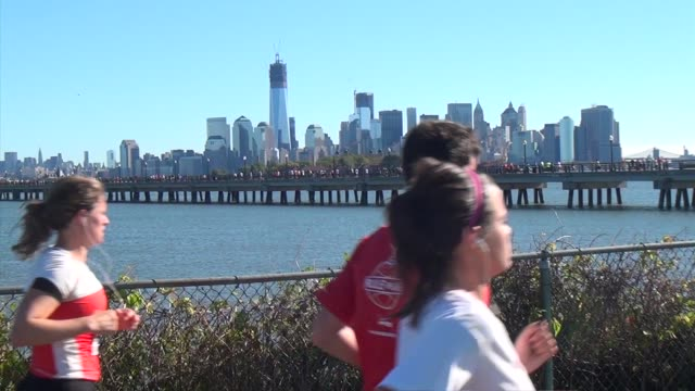 Runners in Road Race head through Liberty State Park in Jersey City with New York Bay and the Hudson River in Background One World Trade Center...