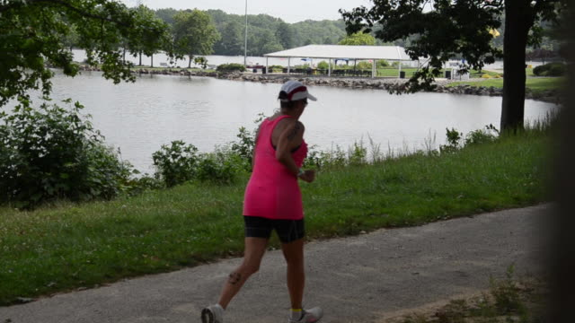 vídeos de stock e filmes b-roll de runners jog past a scenic lake during at the new jersey state triathlon in mercer county park. - triatleta