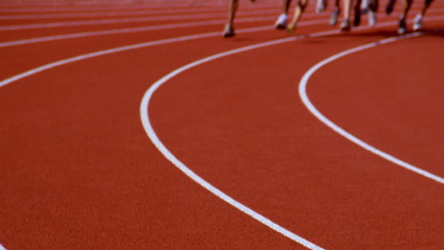 Runners legs race around a track.