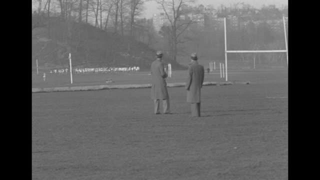 vidéos et rushes de runners on grounds in van cortlandt park race past camera / men in hats and overcoats watch runners in bg / runners coming down road after passing... - 1920 1929