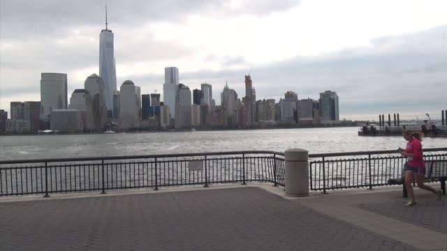 vídeos de stock e filmes b-roll de runners on jersey city riverfront trail with freedom tower, one world trade center or statue of liberty across river - salmini