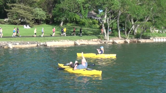 runners on shore cheered with clapping by two kayakers shelter island 10k - salmini stock videos and b-roll footage