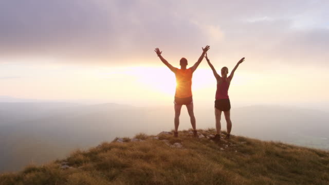 PAN runners on the mountain top raising hands in sunset