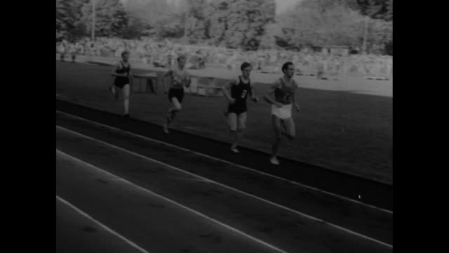 runners racing in mile run / slow motion shot of john landy of australia running / runners race past camera landy in lead / shot of crowd in stands... - men's track stock videos and b-roll footage