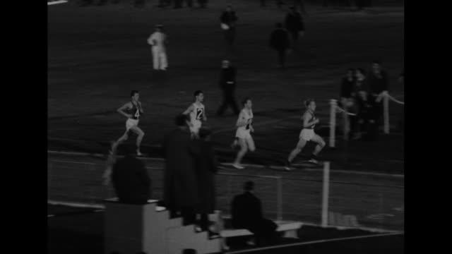 Runners racing / opening ceremony in indoor White City Stadium / shot of crowd in stadium / two shots of runners racing / CU British distance runner...