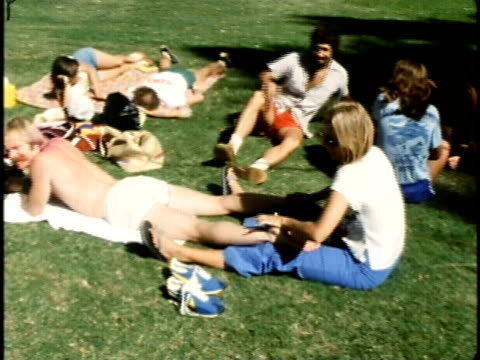 ws runners relaxing on grass after marathon/ ws zi woman massaging man's legs among group of people relaxing on grass/ ms competitor lying on grass... - 1976 stock videos and b-roll footage