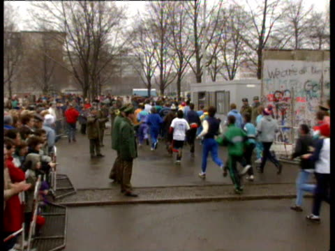 vídeos de stock, filmes e b-roll de 6k runners run through brandenburg gate on new year's day east german guards happily greeting marathon runners and slapping their hands people... - east berlin