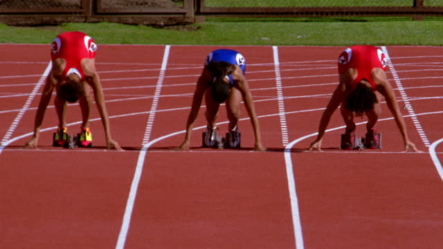 runners spring from their starting blocks at the beginning of a race. - 女子トラック競技点の映像素材/bロール
