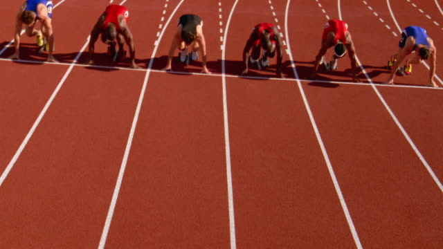 Runners spring from their starting blocks at the beginning of a race.