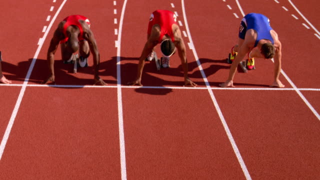 runners spring from their starting blocks at the beginning of a race. - スターティングブロック点の映像素材/bロール