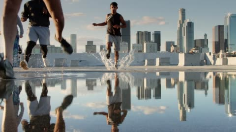 runners sprinting through puddle on los angeles rooftop - five people stock videos & royalty-free footage