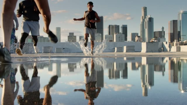 läufer sprinteln auf los angeles rooftop durch puddle - five people stock-videos und b-roll-filmmaterial