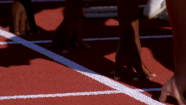 stockvideo's en b-roll-footage met runners squat to touch the starting line at the beginning of a race. - menselijke arm