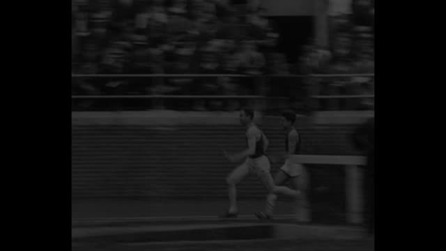 Runners start mile relay race at Penn Relays / runners racing / one runner overtakes another / runners coming down track toward camera with Bill Carr...