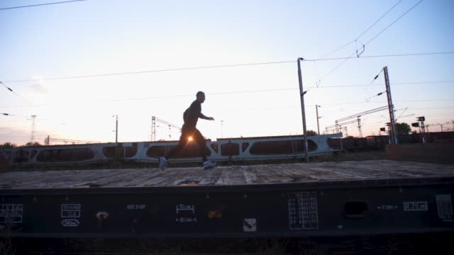 running and jumping on a train vagons - conquering adversity stock videos & royalty-free footage