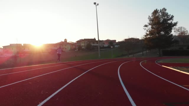 running at sunset - running track - freedom and relaxation - sport and physical activity - pista di atletica leggera video stock e b–roll