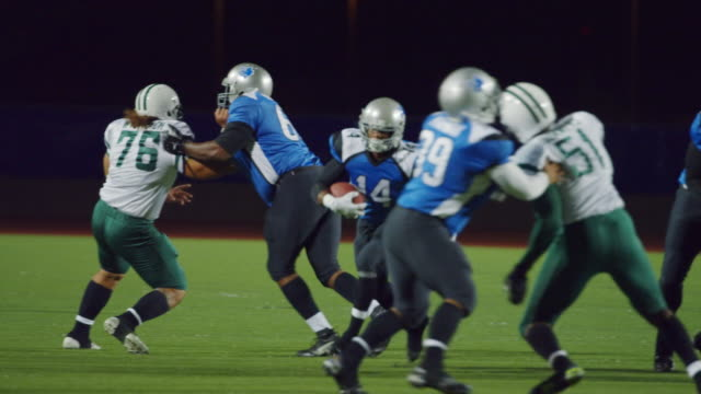 ws slo mo. running back carries football downfield but loses possession of ball in tackle as defending team scramble to recover fumble. - american football ball stock videos & royalty-free footage