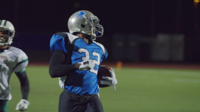 MS SLO MO. Running back carries football into end zone for touchdown as teammates cheer in professional football game.
