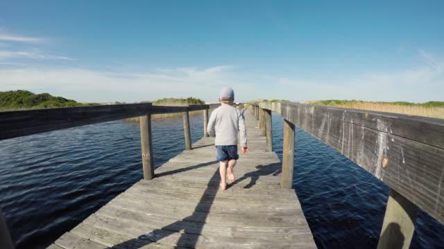 stockvideo's en b-roll-footage met pov uitgevoerd achter een jonge jongen op de houten brug - following moving activity