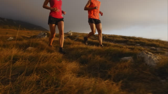 ts slo mo running couple descending at sunset - running shorts stock videos and b-roll footage
