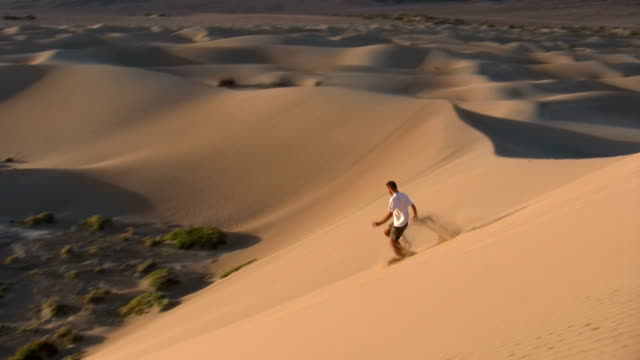 stockvideo's en b-roll-footage met hd: running down a sand dune - death valley national park