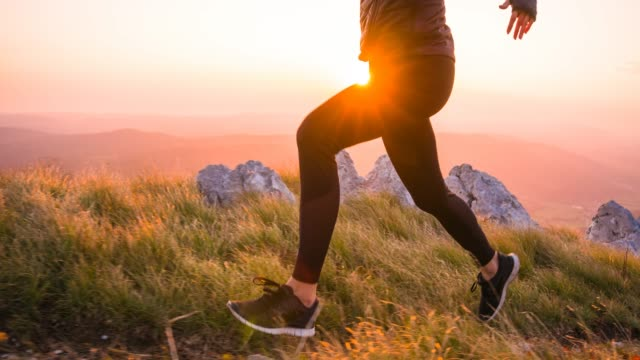 running in the mountains at sunset, brightly lit sky in background - sezione inferiore video stock e b–roll