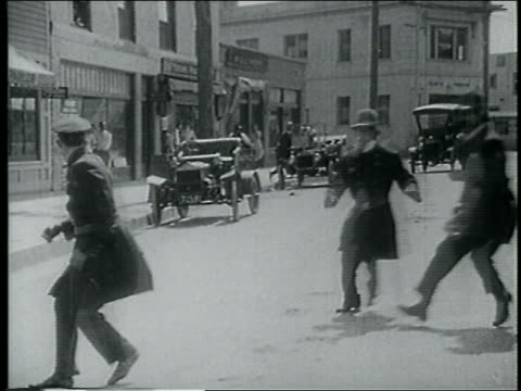 stockvideo's en b-roll-footage met b/w 1915 running keystone kops colliding with each other on street / feature - 1915