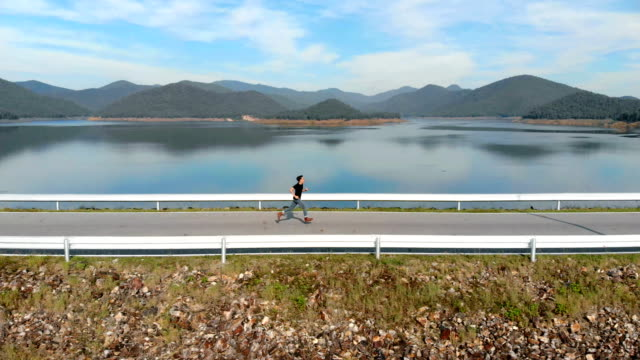 aerial running man on the road with lake and mountain background - carrellata video stock e b–roll