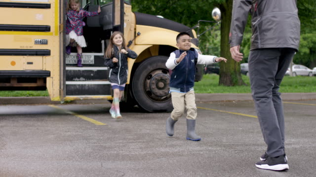 running off of school bus to parents - back to school stock videos & royalty-free footage
