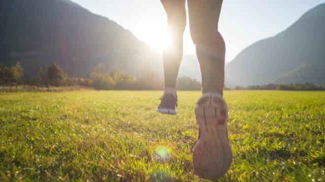 laufen auf einer wiese umgeben von bergen in der schönheit eines frühen morgen sonnenaufgang - jogging stock-videos und b-roll-filmmaterial
