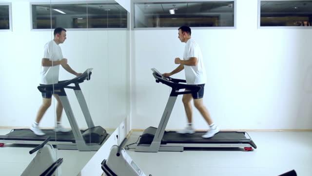 vídeos de stock, filmes e b-roll de running on treadmill in gym. - esteira rolante aparelho de musculação