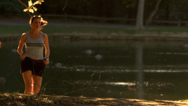 vídeos de stock, filmes e b-roll de running past a pond - self discipline