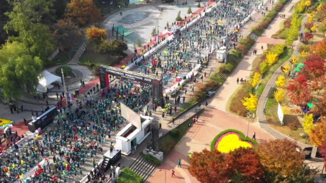 running people at 'chuncheon marathon (chosun ilbo)' event in gongjicheon stream / chuncheon, gangwon-do, south korea - large group of people点の映像素材/bロール